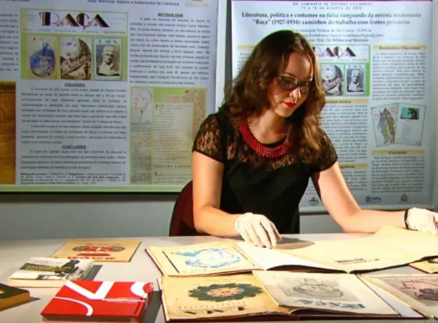 A pesquisadora metendo os óculos nos perdidos de Drummond. Foto: Wilson Aiello